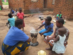 Judith boiling tea to feed family members. Glory (CHW Volunteer) is speaking to her
